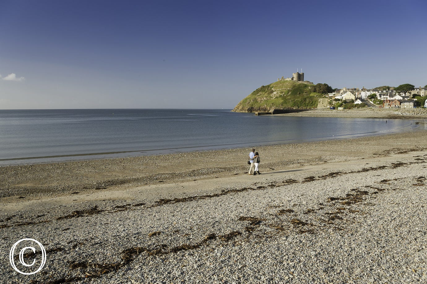 Couple walking on Cricieth beach with Castle in background