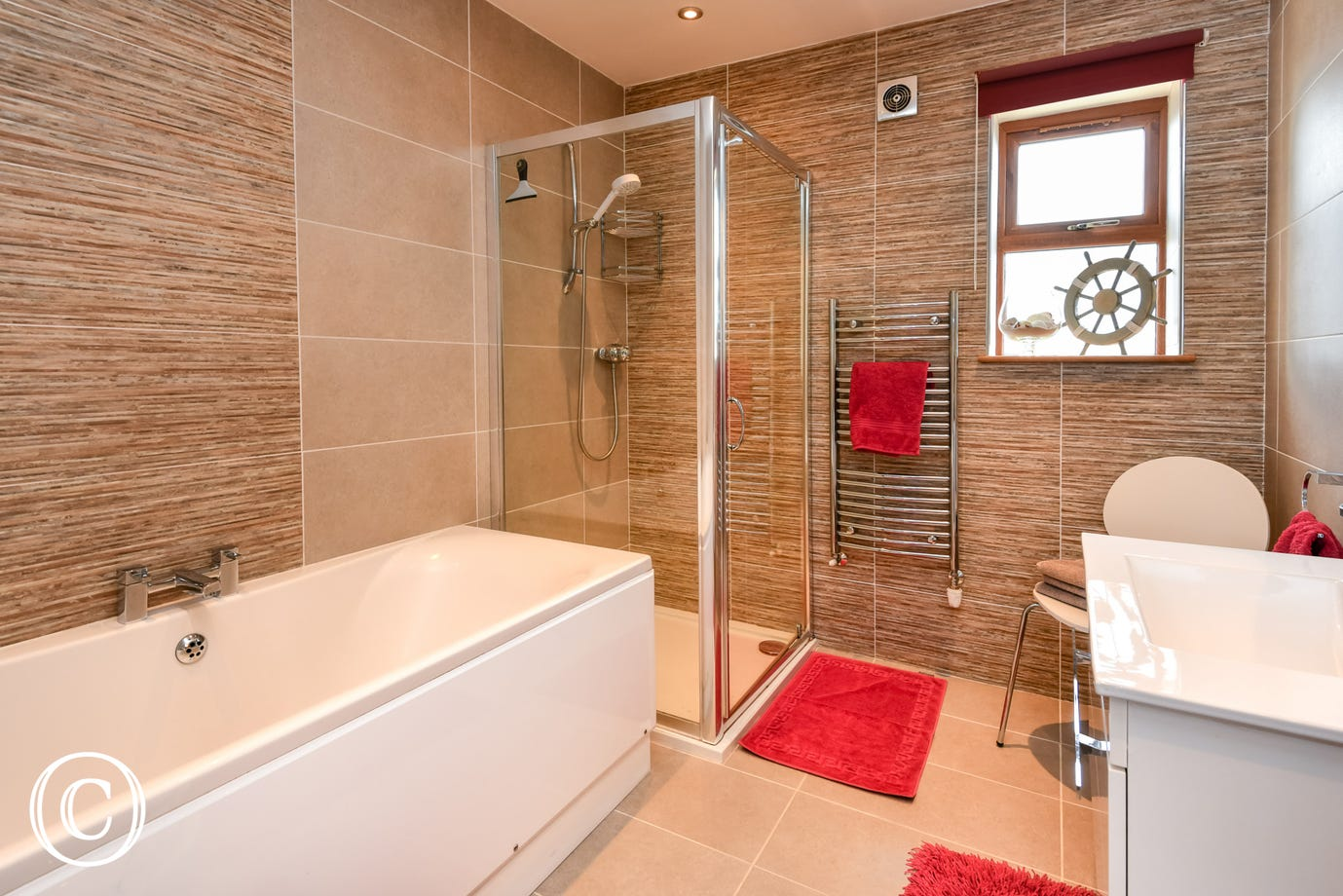 Stylish ground floor bathroom with a low-level shower & deep bath